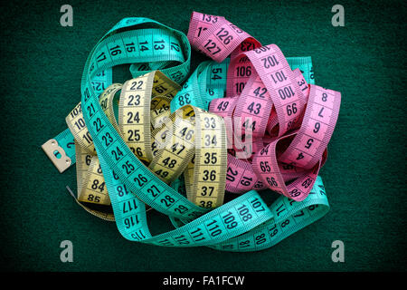 Colorful measuring tapes pile on green background. Close up. - Stock Photo