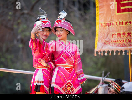 Chinese women dressed in colorful costumes taking a selfie atop float at San Francisco Chinese New Year parade.