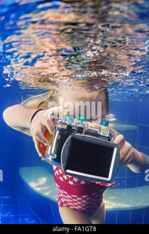 Little baby photographer with camera swim and dive with fun to take funny underwater photo of parent in blue pool.
