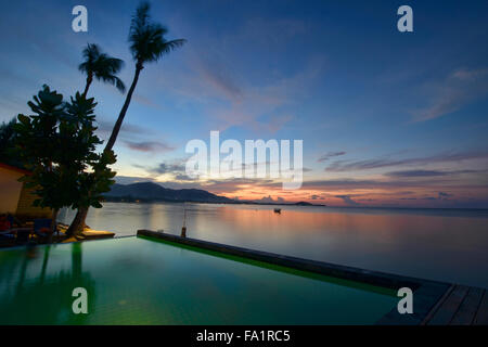 Sunset over an infinity edge pool on Koh Samui island, Thailand - Stock Photo