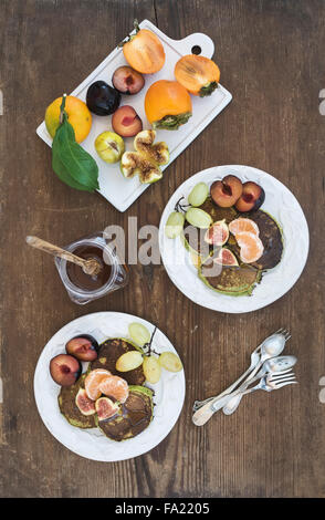 Breakfast set. Homemade zucchini pancakes with fresh plum, tangerine, grapes, figs and honey in white ceramic plates - Stock Photo