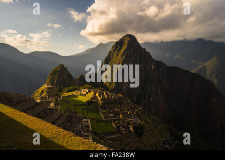 Machu Picchu partially illuminated by the last sunlight. Wide angle view from the terraces with scenic sky and glowing - Stock Photo