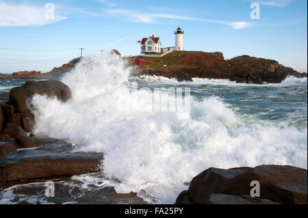 Waves crashing along the rocky shoreline near Nubble lighthouse in Maine at high tide. It is one of the most photographed - Stock Photo