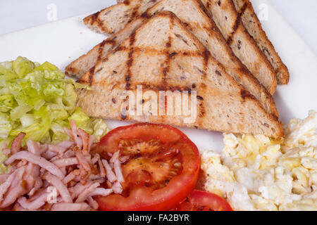 Traditional English breakfast with scrambled eggs, tomatoes, potatoes, toast and fresh salad - Stock Photo