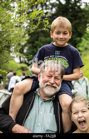 Seven year old boy getting a piggyback ride from his grandfather, with his nine year old sister getting into the - Stock Photo