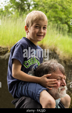 Seven year old boy getting a piggyback ride from his grandfather in Seattle, Washington, USA - Stock Photo