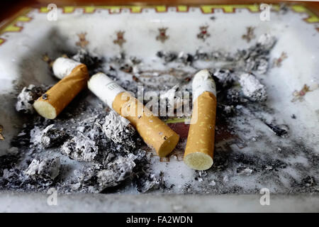 Cigarette butts in an ashtray. - Stock Photo