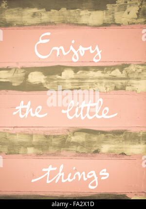 Concept image of ENJOY THE LITTLE THINGS motivational quote hand written on vintage painted wooden wall - Stock Photo