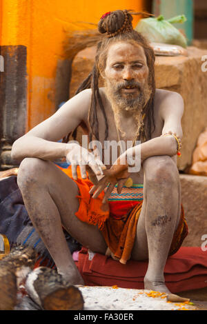 A naga baba sadhu, skin covered in ash, sitting on the ghat along the Ganges river - Stock Photo