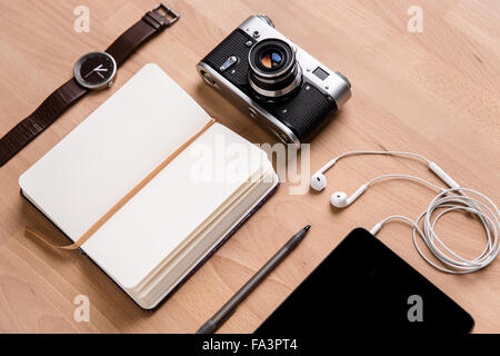 Opened notepad with white blank pages, tablet computer with earphones, old camera watch and pen on wooden table - Stock Photo