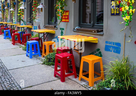 District Mot Vietnamese restaurant and brightly coloured chairs and tables on  pavement, Mulackstrasse, Berlin - Stock Photo