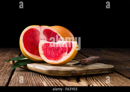 Portion of fresh Grapefruit on an old wooden table (close-up shot) - Stock Photo