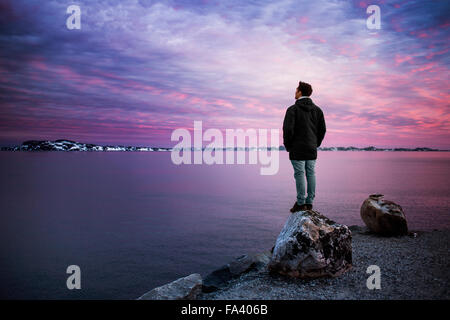 Full length rear view of man standing on rock overlooking sea during sunset - Stock Photo
