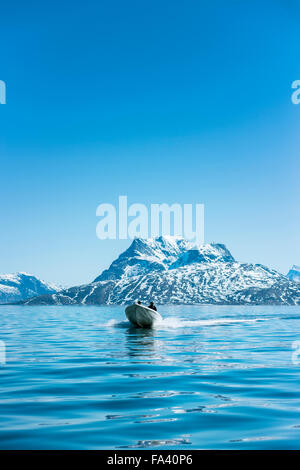 Man in boat sailing on sea against clear blue sky - Stock Photo