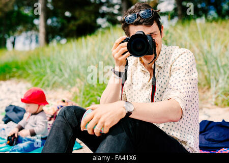 Man photographing using SLR camera - Stock Photo