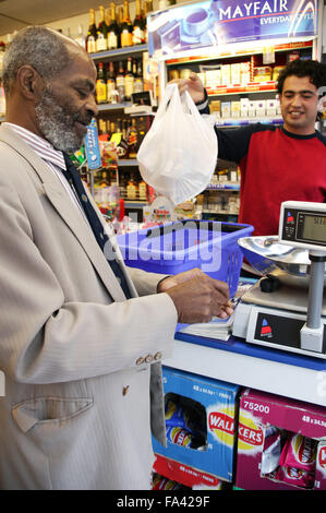Man being served at his local shop; East Midlands Supermarket; Nottingham, - Stock Photo