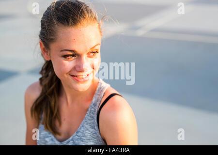 Happy teenage girl looking away at skate park - Stock Photo