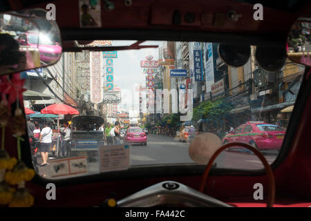Inside a Tuk tuks taxi in the street. View down Thanon Yaowarat road at night in central Chinatown district of Bangkok - Stock Photo