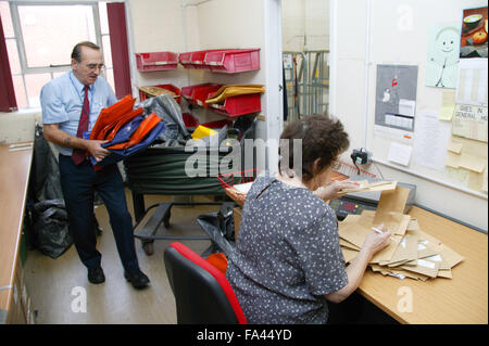 Logistic Operative unloading postal tug and external mail being processed by Clerical Officer in the Hospital post - Stock Photo