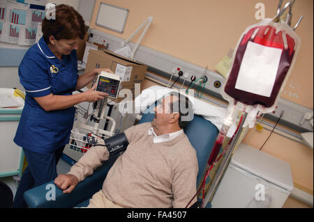 Day Care Manager taking blood pressure whilst Haematology day patient is having a blood transfusion, - Stock Photo
