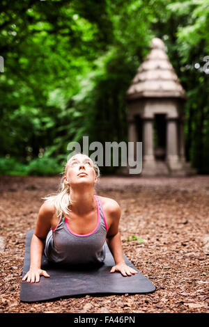 Determined woman practicing yoga at park - Stock Photo