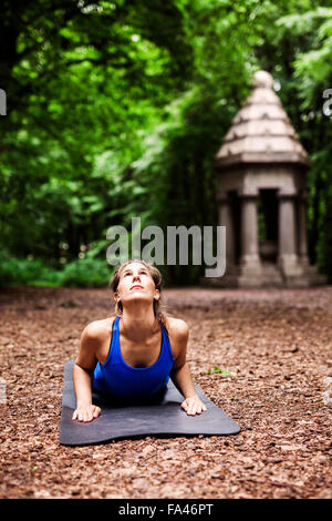 Determined young woman practicing yoga at park - Stock Photo