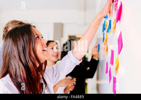 Business people fixing sticky notes at office - Stock Photo