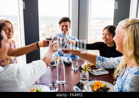 Friends toasting with red wine and enjoying at Sky bar restaurant - Stock Photo