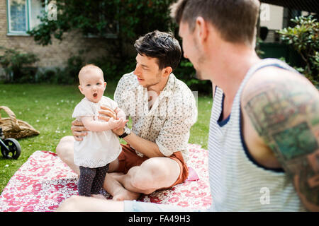 Gay couple looking at baby girl while sitting in yard - Stock Photo