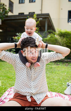 Playful baby girl sitting on father's shoulders at yard - Stock Photo