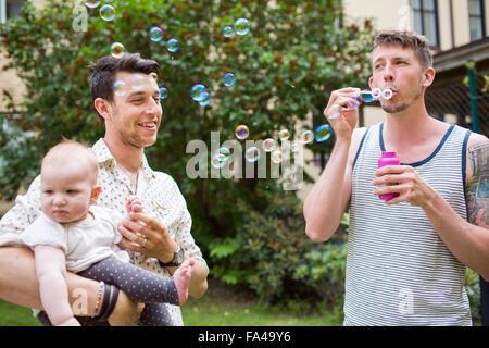 Gay man blowing bubbles while partner carrying baby girl ay yard - Stock Photo