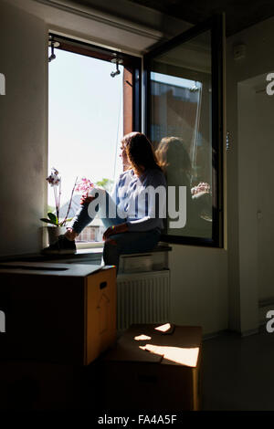 Thoughtful young woman sitting on window sill at new home - Stock Photo