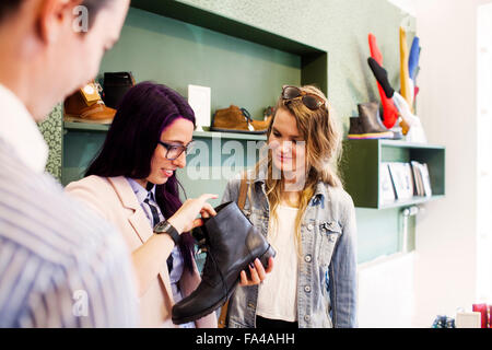 Young women shopping for boot in a boutique - Stock Photo