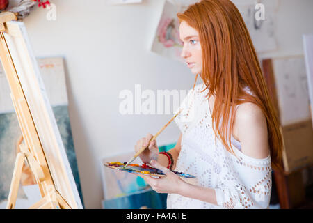 Concentrated pensive young woman painter with long red hair painting on canvas using oil paints in art studio - Stock Photo