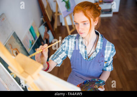 Portrait of concentrated beautiful young woman painter holding art palette and painting on canvas with brush in - Stock Photo