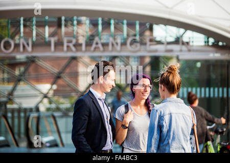 Happy friends waiting outside railroad station - Stock Photo