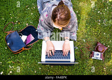 High angle view of freelancer using laptop at park - Stock Photo
