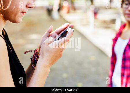 Close-up of girl using smart phone at footpath - Stock Photo