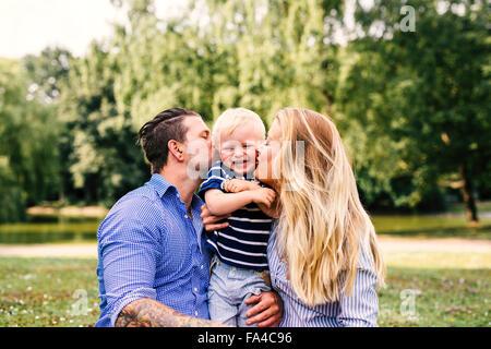 Parents kissing happy son - Stock Photo