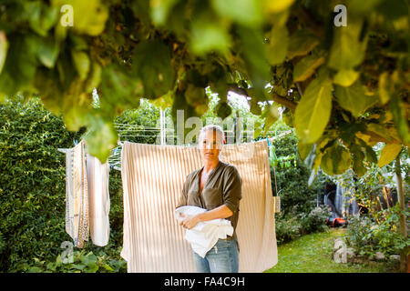 Thoughtful woman drying clothes in garden - Stock Photo
