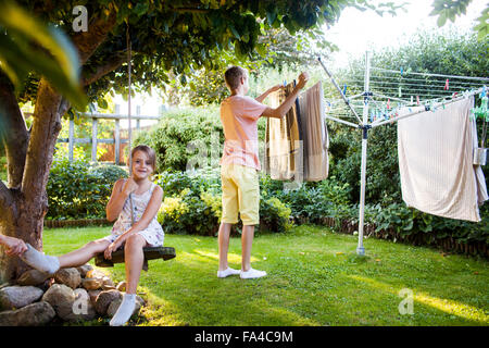 Portrait of girl on swing with brother doing laundry work in background at garden - Stock Photo