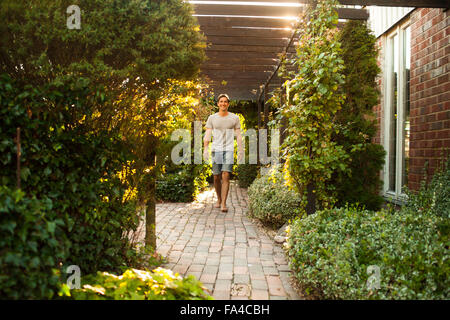 Full length portrait of happy mature man walking in backyard - Stock Photo