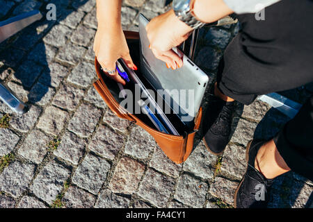 Young businesswoman putting digital tablet in purse while sitting on sidewalk - Stock Photo
