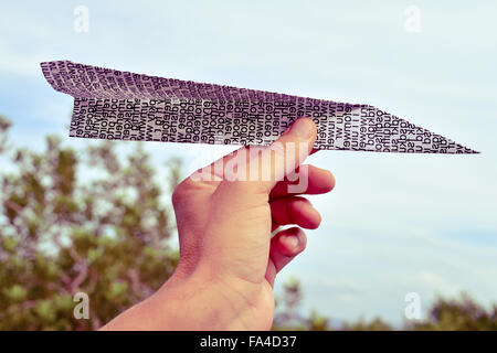 closeup of the hand of a young caucasian man about to throw a paper plane made with a printed paper with non-sense - Stock Photo