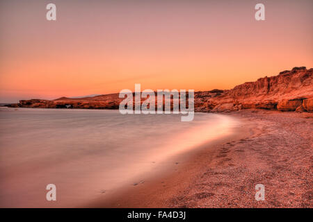 Sunset at a wild beauty beach with eaten by the sea cliffs and unique caves in Karpathos, Greece - Stock Photo