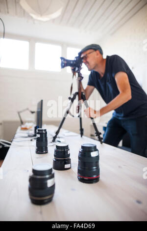 Mid adult photographer using SLR camera while various lenses on table in studio - Stock Photo