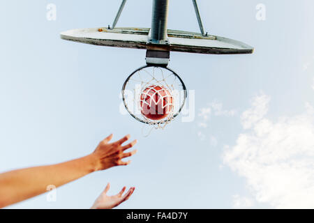 Cropped hands reaching basketball hoop against sky - Stock Photo
