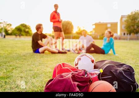 Sports equipment on grass at park with friends relaxing in background during sunset - Stock Photo