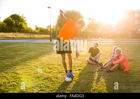 Sporty friends looking at man balancing on soccer ball at park - Stock Photo