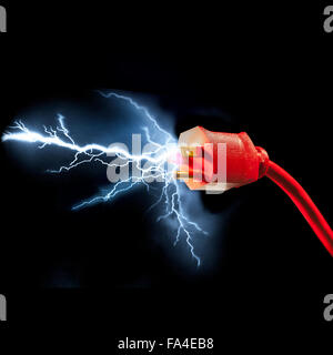 Red electrical plug with sparks flying out on large black background - Stock Photo